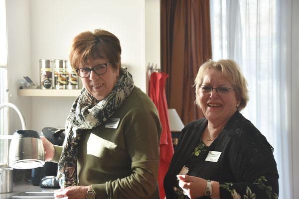 Twee vrijwilligers met koffiekan in hand